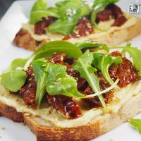 Tosta de hummus con tomates secos y rúcula